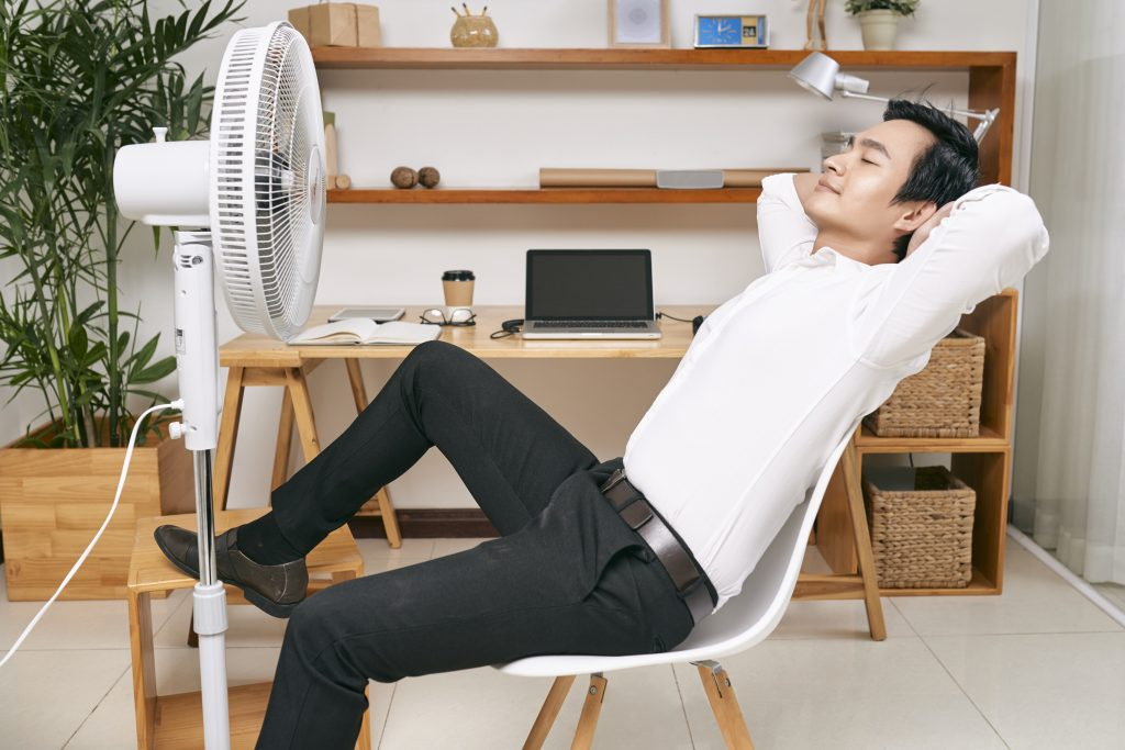 Young Asian office worker resting on chair in front of ventilator and refreshing from heat at office